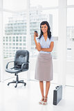 Happy businesswoman texting on her mobile phone
