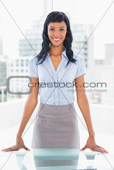 Pleased businesswoman standing at her desk