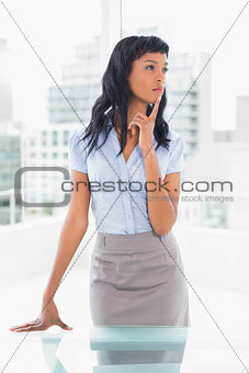 Pensive businesswoman standing at her desk