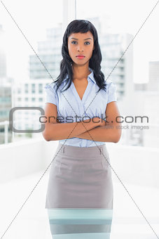 Serious businesswoman posing and crossing her arms