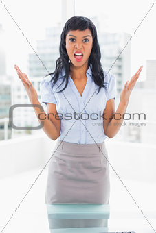 Irritated businesswoman looking at camera and raising her arms
