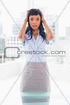 Puzzled businesswoman holding her head