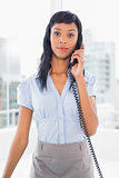 Unsmiling businesswoman answering the telephone