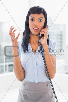 Angry businesswoman answering the phone