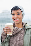Pretty young model in winter clothes holding a coffee
