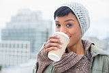 Happy young model in winter clothes enjoying coffee