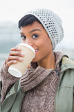 Pleased young model in winter clothes enjoying coffee