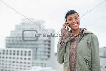 Seductive young model in winter clothes calling someone with her mobile phone