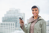 Cheerful young model in winter clothes holding her mobile phone
