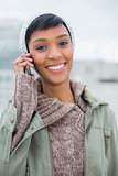 Joyful young model in winter clothes giving a phone call