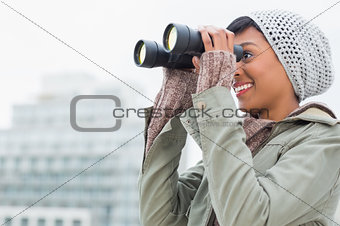 Pretty young model in winter clothes watching the city with binoculars