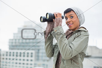 Amazed young model in winter clothes holding binoculars