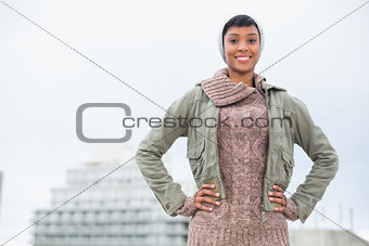Content young model in winter clothes posing hands on the hips