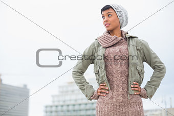 Thoughtful young model in winter clothes posing hands on the hips