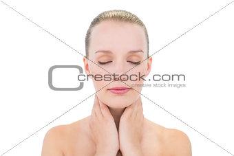 Meditative pretty blonde model holding her neck