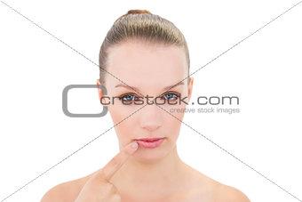 Calm pretty blonde model touching her lip