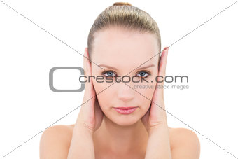 Stressed pretty blonde model blocking her ears