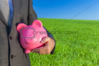 Man Businessman Holding Piggy Bank in Field