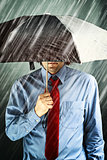Businessman with umbrella in storm