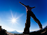 Man opens his arms in the sunshine against blue sky.