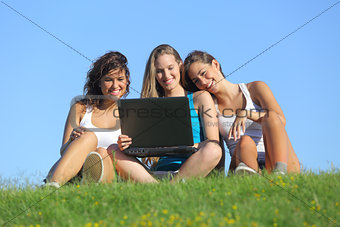 Group of three teenager girls laughing while watching the laptop outdoor