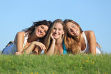 Portrait of a group of three happy teenager girls smiling lying on the grass