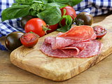 smoked sausage, tomatoes and basil on a wooden cutting board