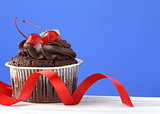 festive (birthday, valentines day) cupcake decorated with chocolate ganache and cherries