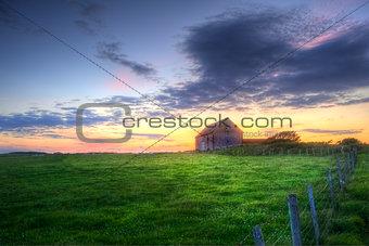 Old barn in landscape at sunset