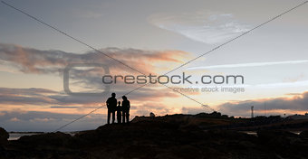 Silhouette of young family walking along deserted beach