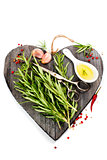 Fresh spices on heart shaped cutting board