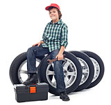 Boy sitting on car tires
