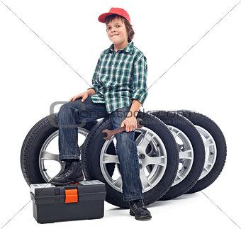 Boy sitting on car tires