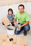 Father and son laying floor tiles together