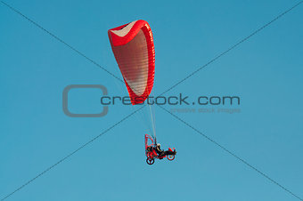 Paragliding flying over the clear blue sky
