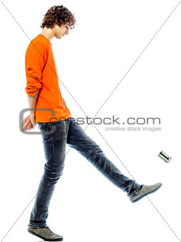 young man walking kicking tin can  side view