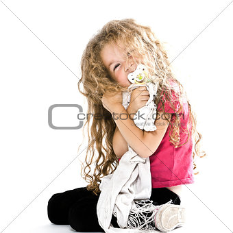 Little girl hugging pacifier and blanket smiling cheerful