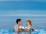 couple lovers swimming pool  seaside drinking coconut milk