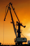 Silhouette of harbor crane at sunrise.