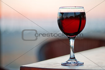 A glass of red wine at sunset.