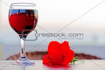 Glass of red wine with a flower at sunset.