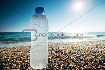 Bottle of fresh water is on the sand by the sea.