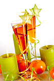 Two orange alcohol cocktails with mandarines and light candles