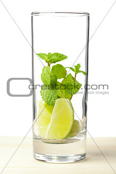 Mojito mix: lime, mint in glass on wood table