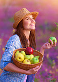 Happy woman with basket of apples