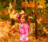 Little girl in autumn forest