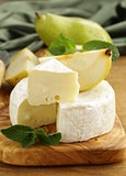 soft brie cheese (camembert) with pears on a wooden board