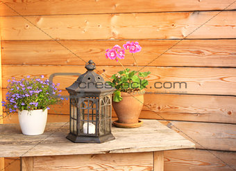 Flowers and old lantern on a wooden table