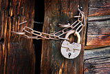 Old rusty padlock on rural wooden gate