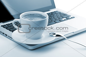 Cappuccino cup on laptop. Toned